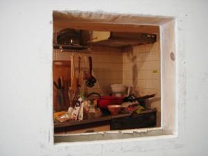 壁に穴を開けたところ。キッチンにいる母親の背中が見えるはず